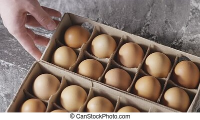 Woman's hand move the box with chicken eggs and takes one ...
