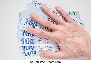 Woman's hand on a bunch of 100 Turkish Lira (TRY) banknotes isolated on white background