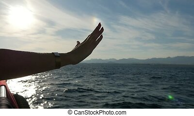 Woman`s hand on a ship`s starboard at splendid sunset in...