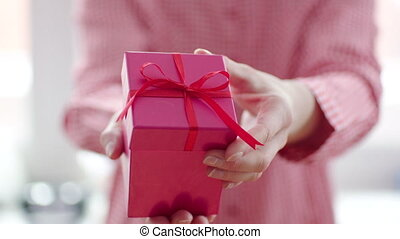 Womans hand opening red gift box with red ribbon