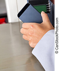 Woman's Hand Placing Smartphone Over Electronic Reader