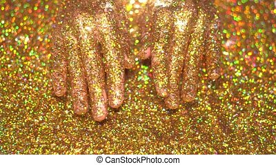 Woman's hand playing with golden glitter