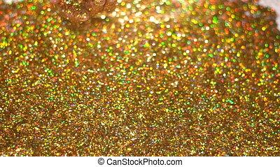 Woman's hand pour golden glitter