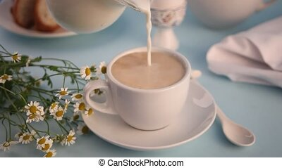 Woman's hand pouring from glass jug into a cup of tea or coffee fresh milk. Breakfast concept.