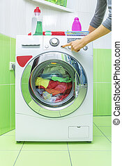 Woman's hand presses a button on the washing machine.