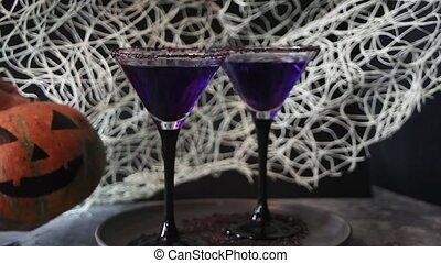 Woman's hand put pumpkin Jack-o'-lantern on the table with glasses of purple cocktail for Halloween party