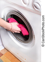 woman's hand puts the laundry