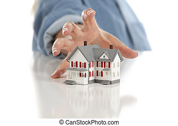 Womans Hand Reaching for Model House on White - Womans Hand...