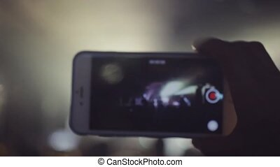 Woman's hand records rock concert on cellphone in the club...