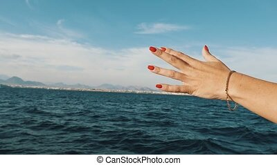 Woman`s hand stretching out to the wavy sea from a ship in...