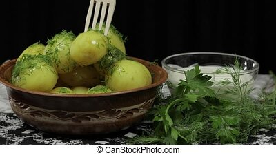 Woman's hand takes boiled new delicious potato using wooden...