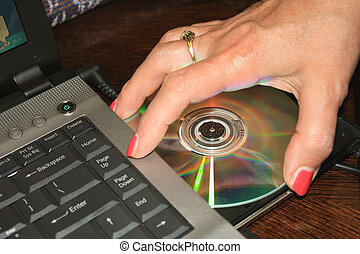 womans hand taking DVD disc from laptop.