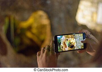 Woman's hand taking photo of local landmark. Panagia, Thassos, Greece
