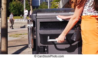 Woman's hand throwing away garbage in public trash can