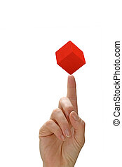 Woman's hand with a red cube on the finger - Woman`s hand...
