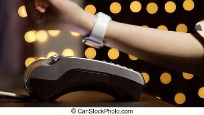 Woman's hand with hand watches using terminal for payment, non-cash transaction, side view. Non-cash payment concept. Pos-terminal on table on black background with yellow light spots.