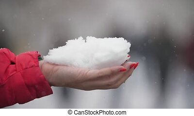 Woman`s hand with makeup keeping a snowball outdoors in...