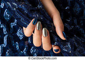 Womans hand with manicure on the creative blue sparkle background