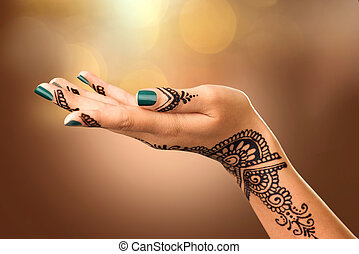 Woman's hand with mehndi tattoo. Hand of Indian bride with black henna tattoos