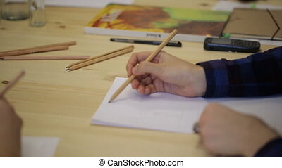Woman's hand with pencil draws on paper sheet in line.