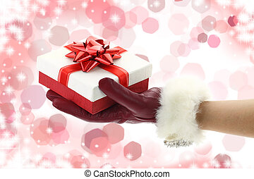 Woman's hand with red glove holding a Christmas gift