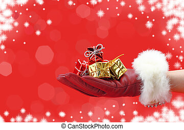 Woman's hand with red glove holding a Christmas gifts
