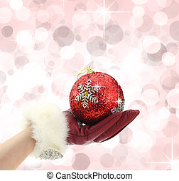 Woman's hand with red glove holding a Christmas ball