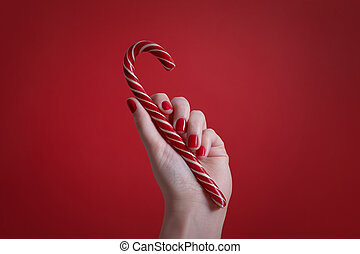 Woman's hand with red manicure nails holding christmas candy cane on red background