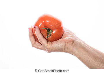 Woman's hand with red nail squeezing tomato on a white background