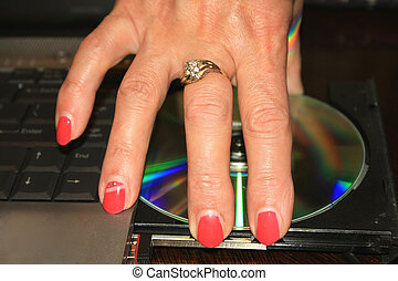 woman's hand with red nails taking DVD disc from PC.