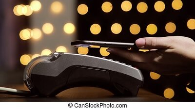 Woman's hand with smartphone using terminal for payment, non-cash transaction, side view. Non-cash payment concept. Pos-terminal on table on black background with yellow light spots.