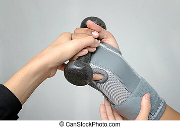 Woman's hand with wrist support lifting dumbbell for hand exercise ,rehabilitation hand