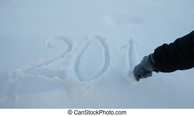 woman's hand writes 2018 sign on the white snow - woman's...