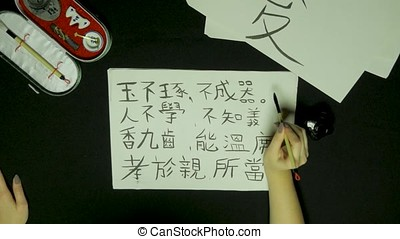 Woman's hand writing chinese calligraphy. Female hand...