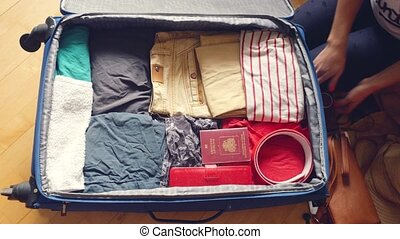 Woman's hands are packing suitcase for a journey and...