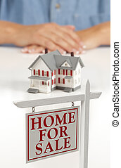 Womans Hands Behind House and Real Estate Sign in Front