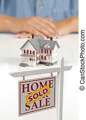 Womans Hands Behind House and Sold Real Estate Sign