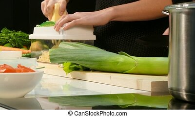 Woman's hands cut the leeks and chop the cheese