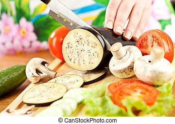 Woman's hands cutting aubergine eggplant