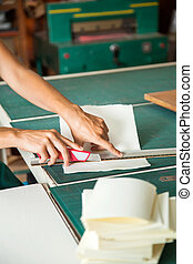 Cropped image of woman's hands cutting paper using blade on table in factory