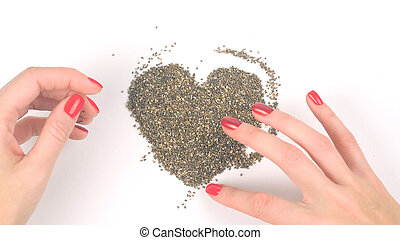 Woman's hands forming heart from chia seeds in backward play