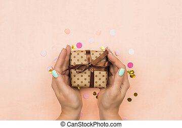 Woman's hands give a gift on a pink background. Template for blog or advertisement. Holiday gift on pink pastel background with multicolored confetti
