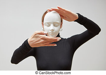 Woman's hands hold gypsum mask. Girl in a black jumper with plaster sculpture on a white background. Concept The masks we wear.