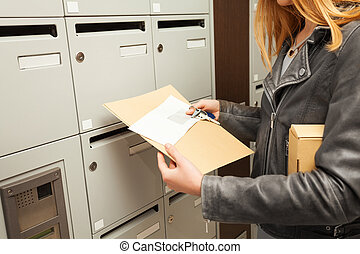 Woman's hands holding blanked envelopes and box