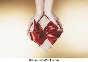 Woman's hands holding craft paper gift box