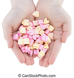 Woman's hands holding heart candy, marshmallows isolated on white background