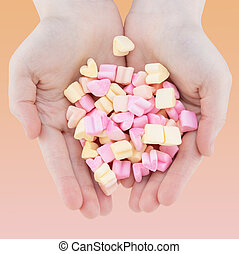 Woman's hands holding heart candy, marshmallows on pastel background