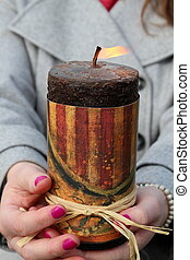Woman's hands holding lit candle
