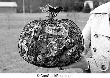 Woman's hands holding metal pumpkin