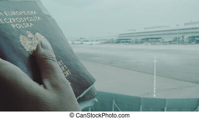 Woman's hands holding passports at the airport